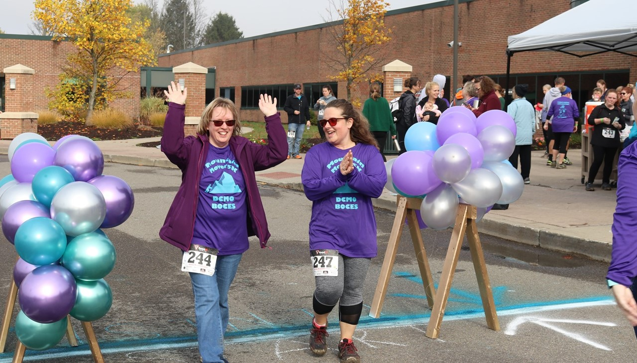 two women cross finish line between two bundles of purple, green, and white balloons