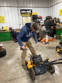 image of a student working with small engine